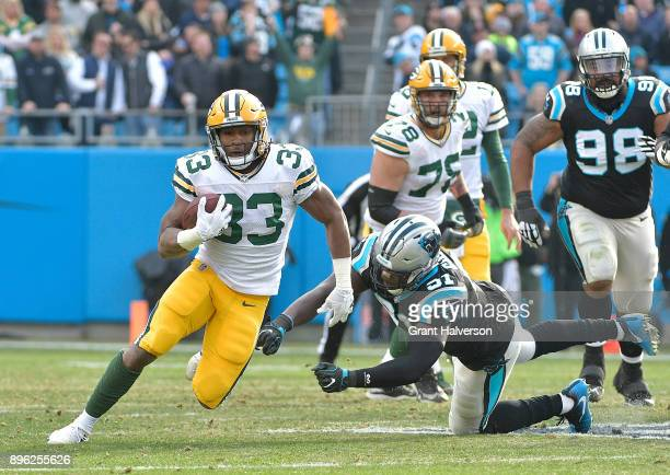 Aaron Jones of the Green Bay Packers runs against the Carolina Panthers during their game at Bank of America Stadium on December 17 2017 in Charlotte...