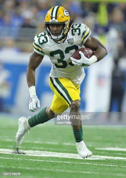 Aaron Jones of the Green Bay Packers runs for a first down during the first quarter of the game against the Detroit Lions at Ford Field on October 7...