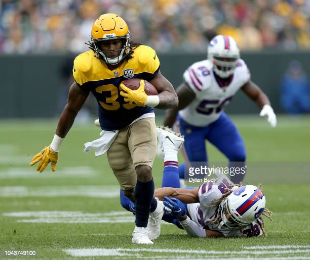 Aaron Jones of the Green Bay Packers runs past Ryan Lewis of the Buffalo Bills during the second quarter of a game at Lambeau Field on September 30...