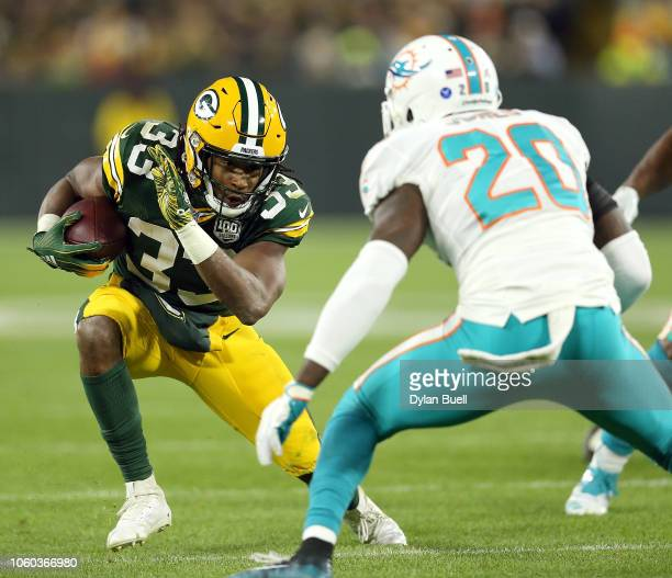 Aaron Jones of the Green Bay Packers runs the ball against Reshad Jones of the Miami Dolphins during the second half of a game at Lambeau Field on...
