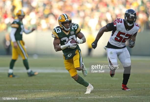 Aaron Jones of the Green Bay Packers runs the ball for a touchdown during the second half of a game against the Atlanta Falcons at Lambeau Field on...