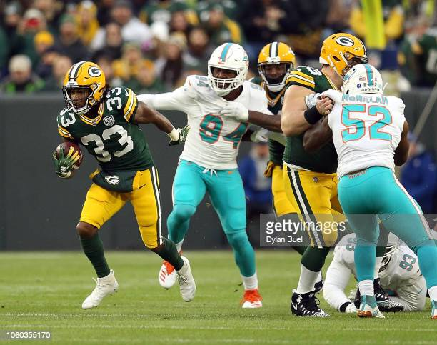 Aaron Jones of the Green Bay Packers runs the ball past Miami Dolphins defenders during the first half of a game at Lambeau Field on November 11 2018...