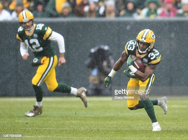 Aaron Jones of the Green Bay Packers runs with the ball during the first half of a game against the Arizona Cardinals at Lambeau Field on December 2...