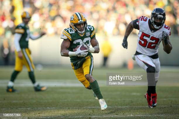 Aaron Jones of the Green Bay Packers runs with the ball in the third quarter against the Atlanta Falcons at Lambeau Field on December 09 2018 in...