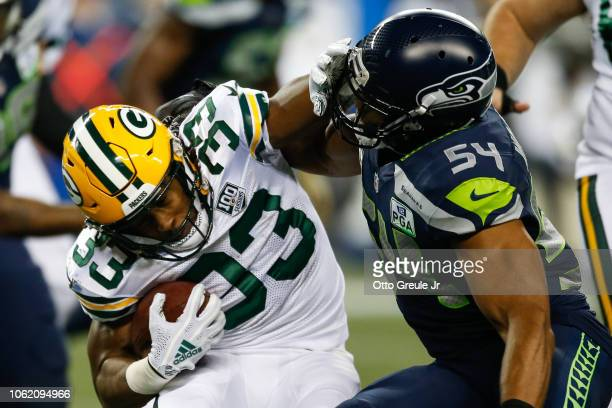 Aaron Jones of the Green Bay Packers runs with the ball past Bobby Wagner of the Seattle Seahawks in the second quarter against the Seattle Seahawks...