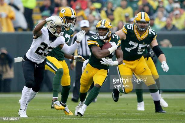 Aaron Jones of the Green Bay Packers runs with the ball while being chased by Marshon Lattimore of the New Orleans Saints in the first quarter at...