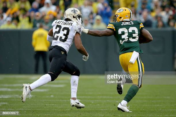Aaron Jones of the Green Bay Packers runs with the ball while being chased by Marshon Lattimore of the New Orleans Saints in the third quarter at...