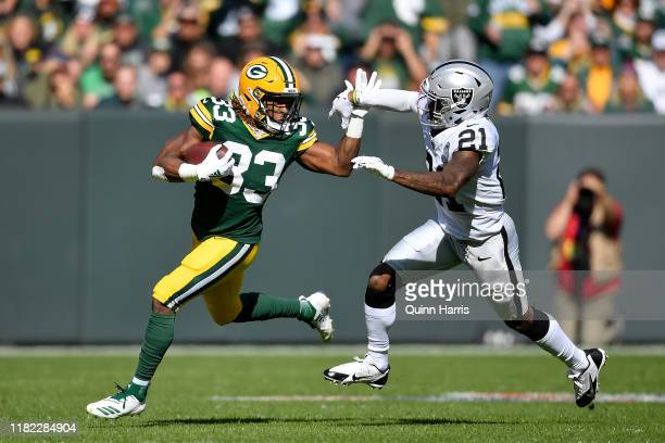 Aaron Jones of the Green Bay Packers runs with the football in the first quarter against Gareon Conley of the Oakland Raiders at Lambeau Field on...