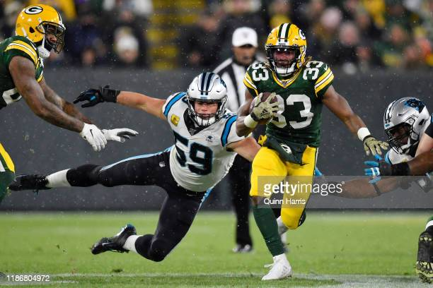 Aaron Jones of the Green Bay Packers runs with the football in the second half against Luke Kuechly of the Carolina Panthers at Lambeau Field on...