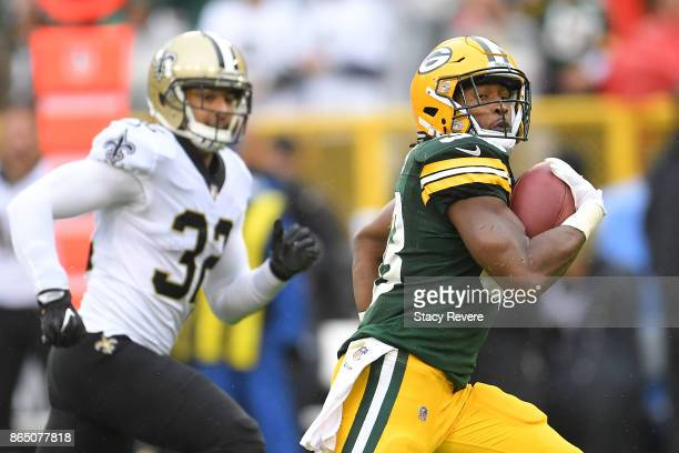 Aaron Jones of the Green Bay Packers rushes for a touchdown against the New Orleans Saints during the first quarter at Lambeau Field on October 22...