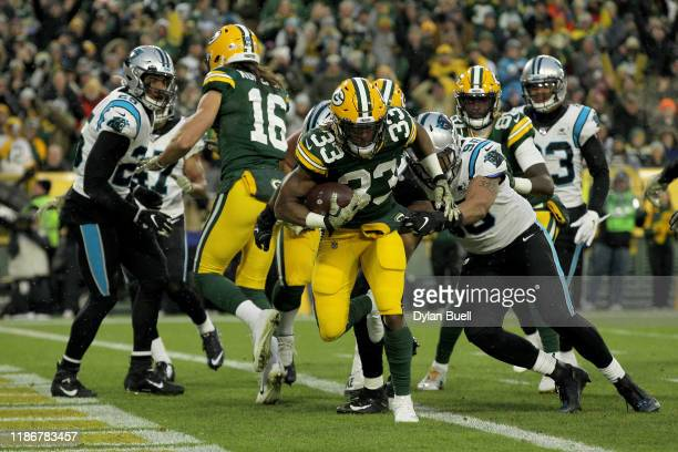 Aaron Jones of the Green Bay Packers scores a 5 yard touchdown against the Carolina Panthers during the first quarter in the game at Lambeau Field on...