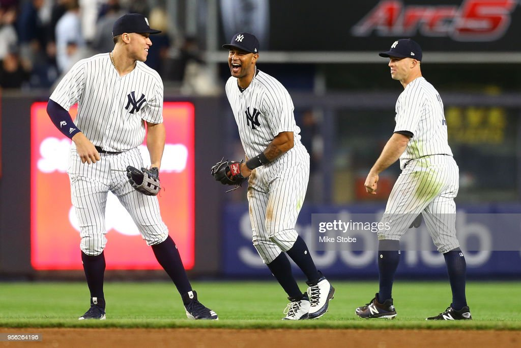 Aaron Judge #99, Aaron Hicks #31 and Brett Gardner #11 of the New York Yankees celebrate after defeating the Boston Red Sox 3-2 at Yankee Stadium on May 8, 2018 in the Bronx borough of New York City.