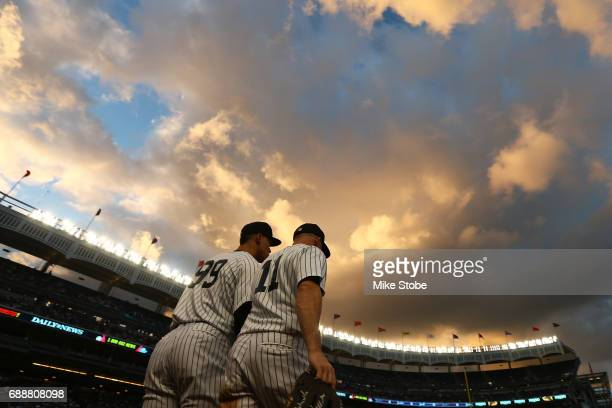 Aaron Judge and Brett Gardner of the New York Yankees take the field in the third inning against the Oakland Athletics at Yankee Stadium on May 26...