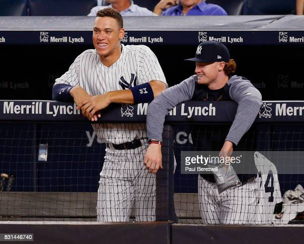 Aaron Judge and Clint Frazier of the New York Yankees watch from the top of the dugout steps in an MLB baseball game against the Boston Red Sox on...