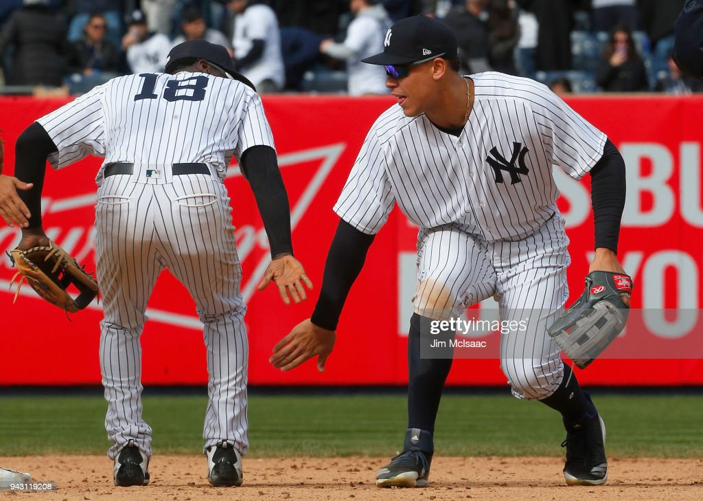 Aaron Judge #99 and Didi Gregorius #18 of the New York Yankees celebrate after defeating the Baltimore Orioles at Yankee Stadium on April 7, 2018 in the Bronx borough of New York City.