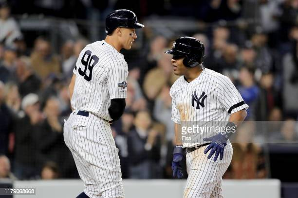 Aaron Judge and Edwin Encarnacion of the New York Yankees celebrate after scoring off of a RBI single hit by Gleyber Torres against Jose Berrios of...
