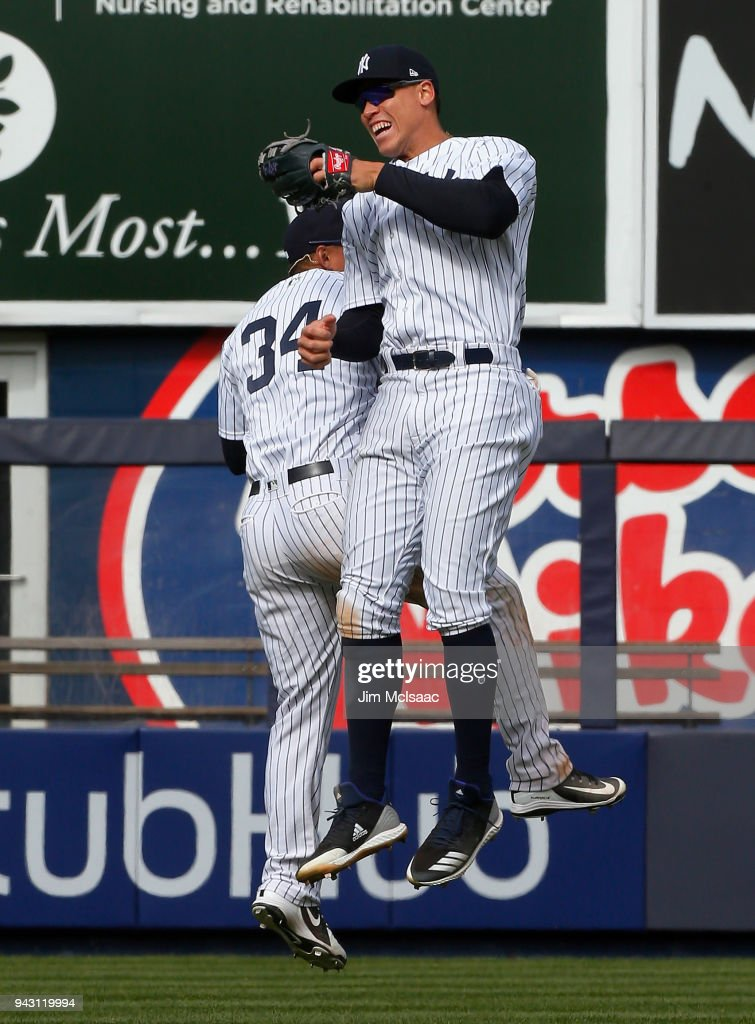 Aaron Judge #99 and Jace Peterson #34 of the New York Yankees celebrate after defeating the Baltimore Orioles at Yankee Stadium on April 7, 2018 in the Bronx borough of New York City.