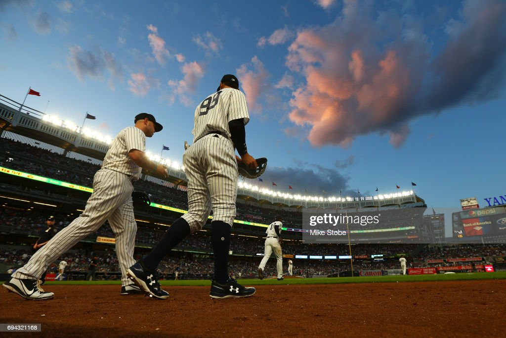 Aaron Judge #99 and Matt Holliday #17 of the New York Yankees take the field for the start of the second inning against the Baltimore Orioles at Yankee Stadium on June 9, 2017 in the Bronx borough of New York City.