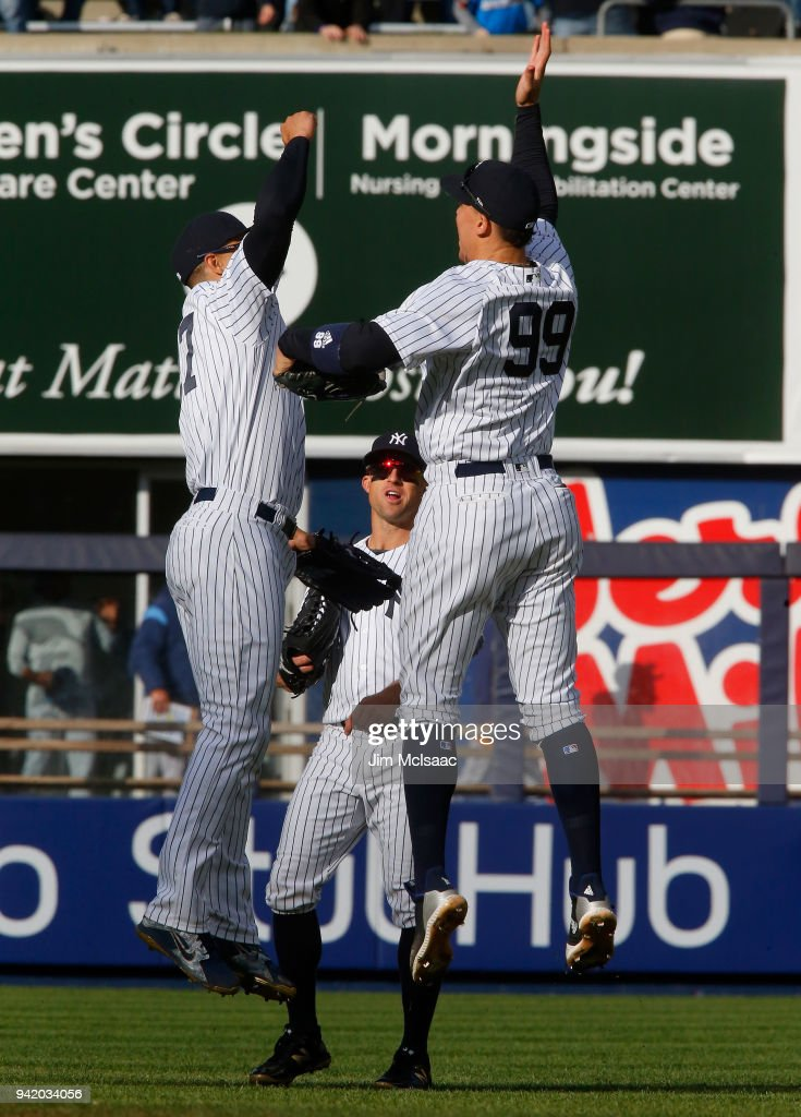 Aaron Judge #99, Giancarlo Stanton #27 and Brett Gardner #11 of the New York Yankees celebrate after defeating the Tampa Bay Rays at Yankee Stadium on April 4, 2018 in the Bronx borough of New York City.