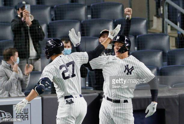 Aaron Judge high-fives Giancarlo Stanton of the New York Yankees after Stanton hit grand slam during the fifth inning against the Baltimore Orioles...