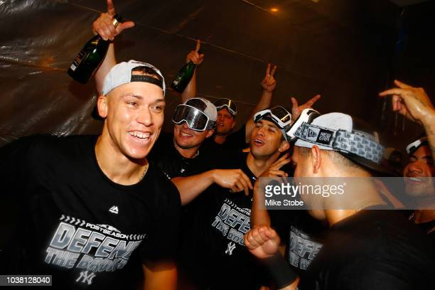 Aaron Judge, Luke Voit and Gary Sanchez of the New York Yankees celebrates clinching a playoff spot after defeating the Baltimore Orioles 3-2 in...