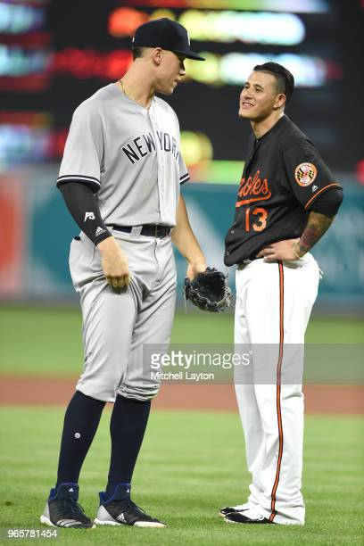 Aaron Judge of the New York Yankees and Manny Machado of the Baltimore Orioles talk between inning pitches during a baseball game at Oriole Park at...