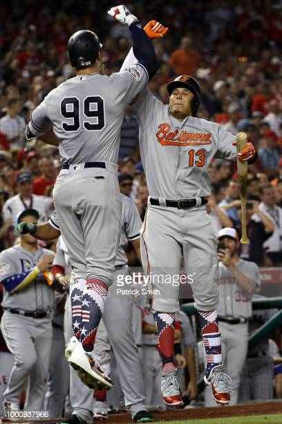 Aaron Judge of the New York Yankees and the American League celebrates with Manny Machado of the Baltimore Orioles and the American League after...