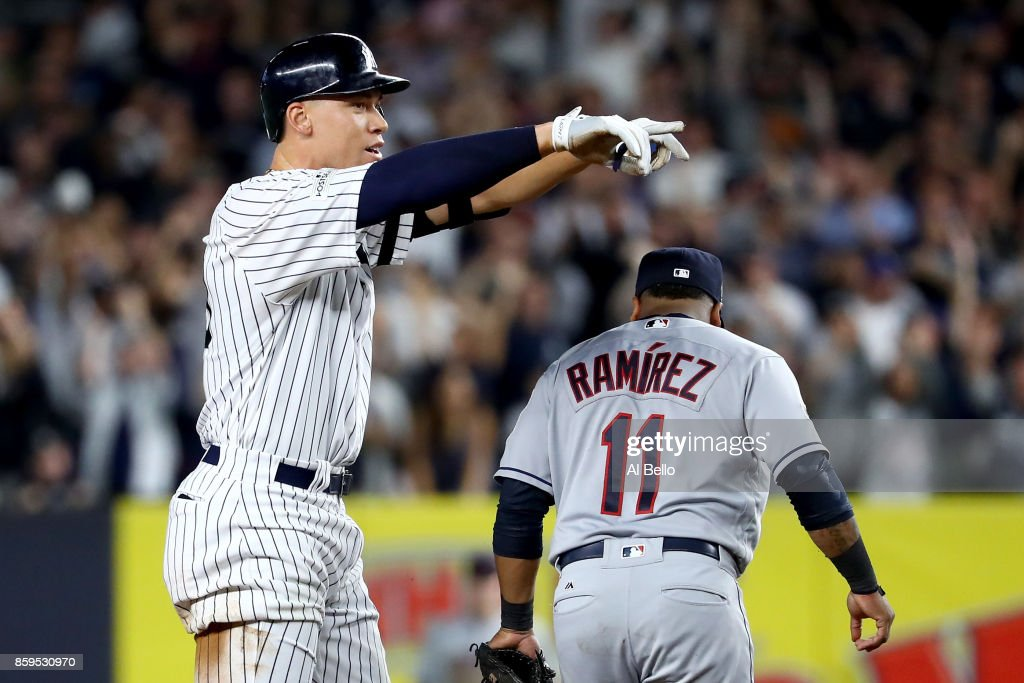 Aaron Judge #99 of the New York Yankees celebrates from second base after hitting a double to left field to score Brett Gardner #11 and Aaron Hicks #31 against Trevor Bauer #47 of the Cleveland Indians during the second inning in Game Four of the American League Divisional Series at Yankee Stadium on October 9, 2017 in the Bronx borough of New York City.
