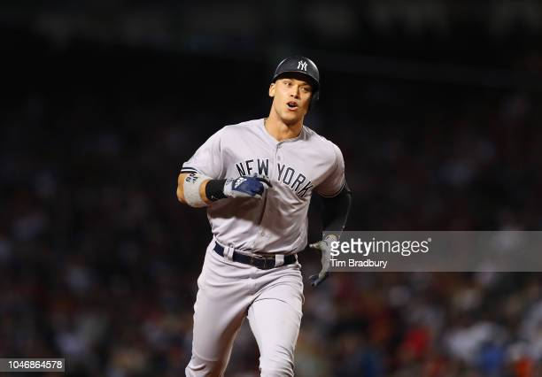 Aaron Judge of the New York Yankees celebrates his solo home run as he rounds third base during the first inning of Game Two of the American League...