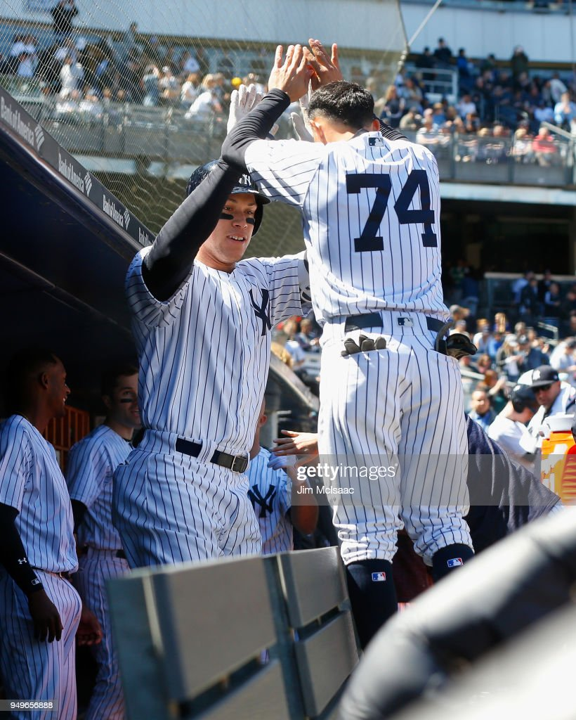 Aaron Judge #99 of the New York Yankees celebrates his third inning two run home run against the Toronto Blue Jays with teammate Ronald Torreyes #74 in the dugout at Yankee Stadium on April 21, 2018 in the Bronx borough of New York City.