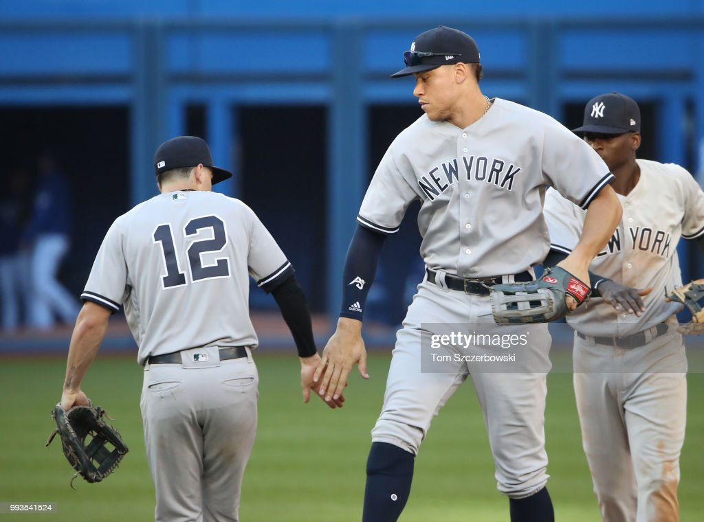 Aaron Judge #99 of the New York Yankees celebrates their victory with Tyler Wade #12 during MLB game action against the Toronto Blue Jays at Rogers Centre on July 7, 2018 in Toronto, Canada.