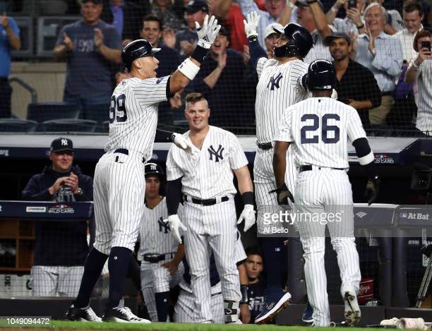 Aaron Judge of the New York Yankees celebrates with Aaron Hicks and Andrew McCutchen after hitting a two run home run in the first inning against the...