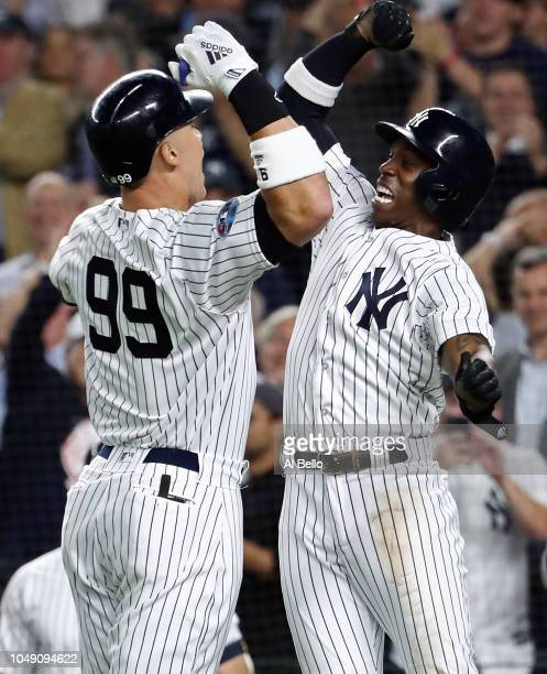 Aaron Judge of the New York Yankees celebrates with Andrew McCutchen after hitting a two run home run in the first inning against the Oakland...