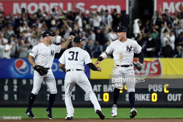 Aaron Judge of the New York Yankees celebrates with Brett Gardner and Aaron Hicks after defeating the Oakland Athletics by a score of 72 to win the...