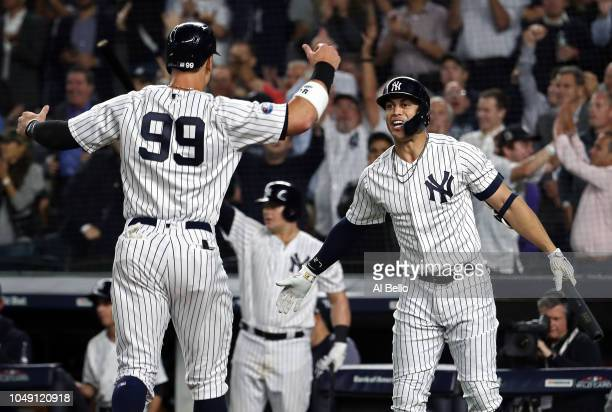 Aaron Judge of the New York Yankees celebrates with Giancarlo Stanton after scoring a run in the sixth inning against the Oakland Athletics during...