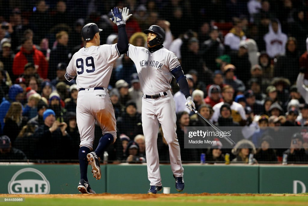 Aaron Judge #99 of the New York Yankees celebrates with Giancarlo Stanton #27 after hitting a home run during the fifth inning against the Boston Red Sox at Fenway Park on April 10, 2018 in Boston, Massachusetts.