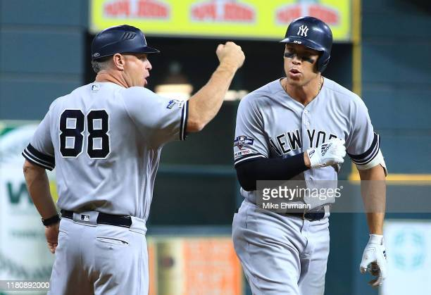 Aaron Judge of the New York Yankees celebrates with third base coach Phil Nevin after hitting a two-run home run during the fourth inning against the...