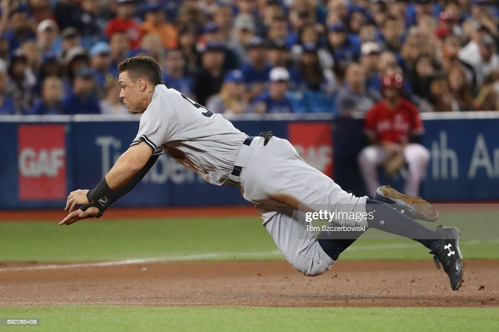 Aaron Judge #99 of the New York Yankees dives safely into third base as he advances from first base on a throwing error in the fourth inning during MLB game action against the Toronto Blue Jays at Rogers Centre on June 4, 2017 in Toronto, Canada.