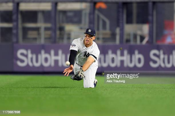 Aaron Judge of the New York Yankees dives to make the catch during the third inning of the ALDS Game 1 between the Minnesota Twins and the New York...