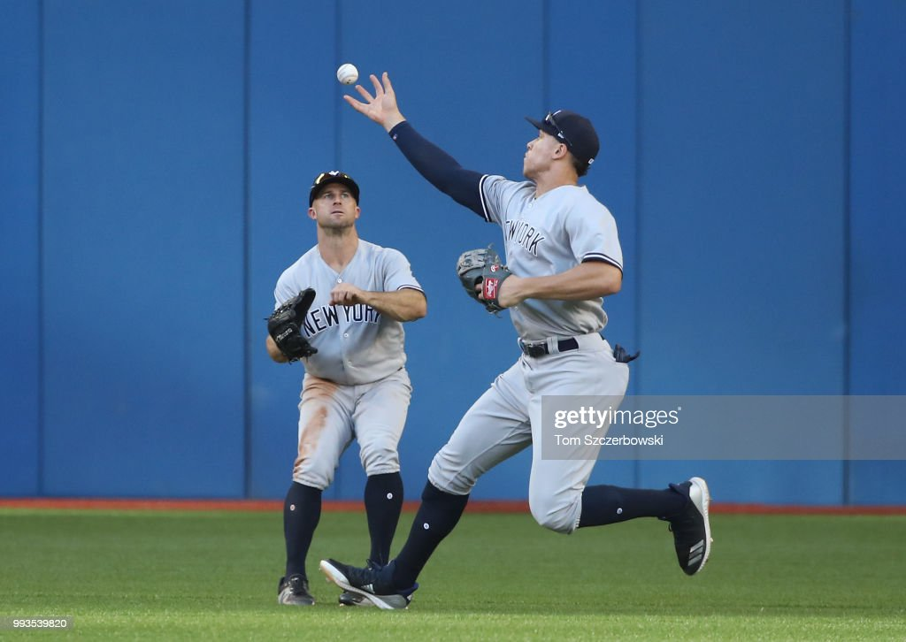 Aaron Judge #99 of the New York Yankees fields a high-hop double hit by Curtis Granderson #18 of the Toronto Blue Jays as Brett Gardner #11 watches in the seventh inning during MLB game action at Rogers Centre on July 7, 2018 in Toronto, Canada.