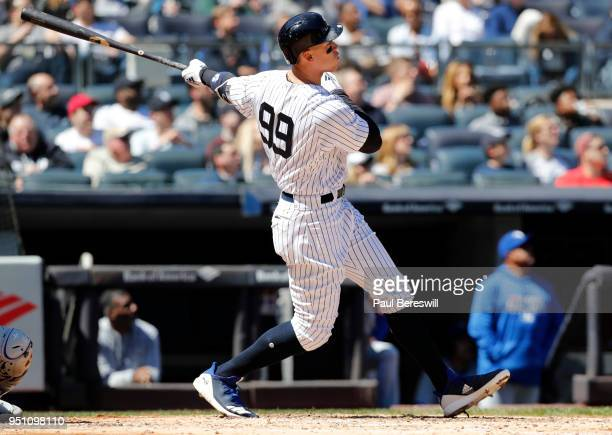 Aaron Judge of the New York Yankees follows through as he hits his 62nd career home run to become the fastest player to reach 62 home runs in his...