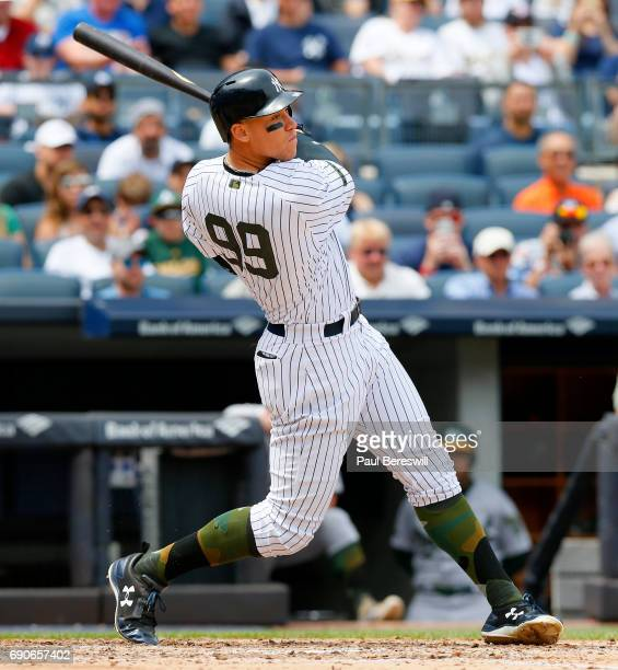 Aaron Judge of the New York Yankees follows through watching his first major league grand slam home run in the third inning of an MLB baseball game...