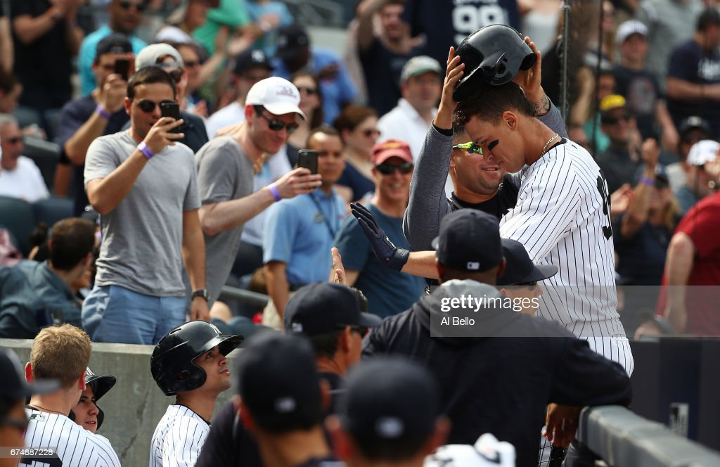 Aaron Judge #99 of the New York Yankees has his helmet removed by Gary Sanchez after his two-run home run against the Baltimore Orioles in the seventh inning during their game at Yankee Stadium on April 29, 2017 in New York City.