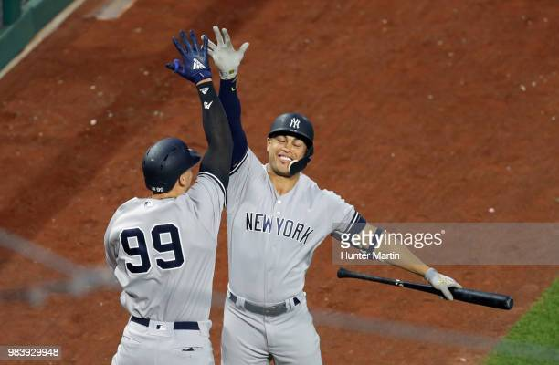Aaron Judge of the New York Yankees highfives Giancarlo Stanton after hitting a solo home run in the fifth inning during a game against the...
