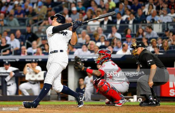 Aaron Judge of the New York Yankees hits a home run as catcher Martin Maldonado of the Los Angeles Angels and umpire Larry Vanover watch in the 5th...
