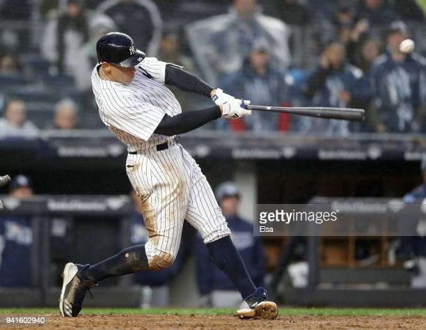 Aaron Judge of the New York Yankees hits a single in the seventh inning against the Tampa Bay Rays during Opening Day at Yankee Stadium on April 3...