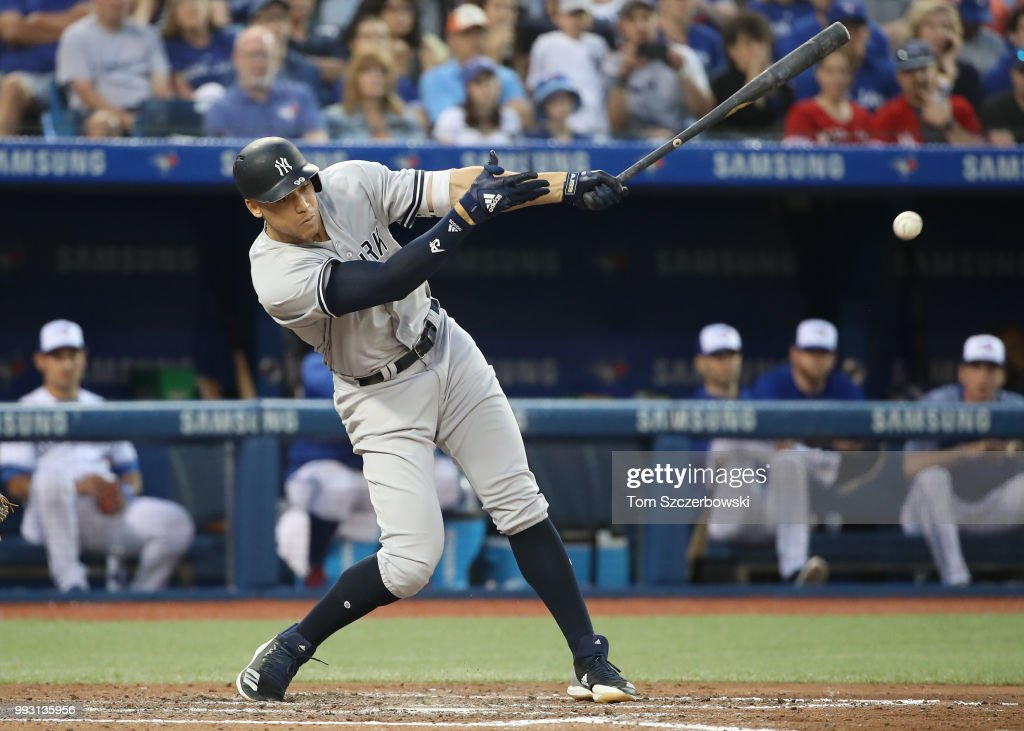 Aaron Judge #99 of the New York Yankees hits a soft infield single in the fifth inning during MLB game action against the Toronto Blue Jays at Rogers Centre on July 6, 2018 in Toronto, Canada.