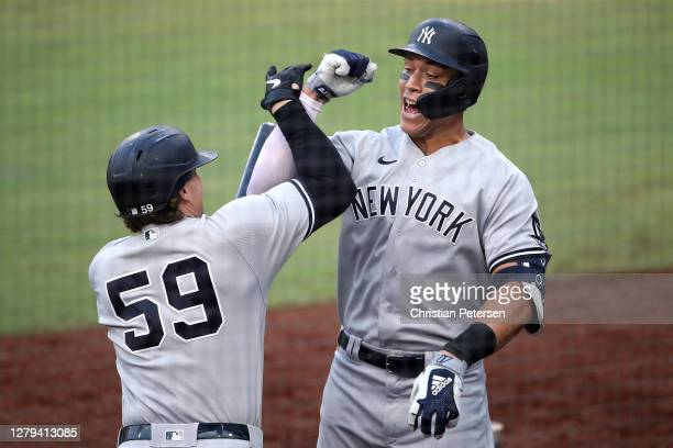 Aaron Judge of the New York Yankees is congratulated by Luke Voit after hitting a solo home run against the Tampa Bay Rays during the fourth inning...