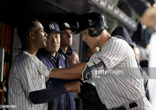 Aaron Judge of the New York Yankees is congratulated by Miguel Andujar in the dugout after he hit a solo home run in the seventh inning against the...