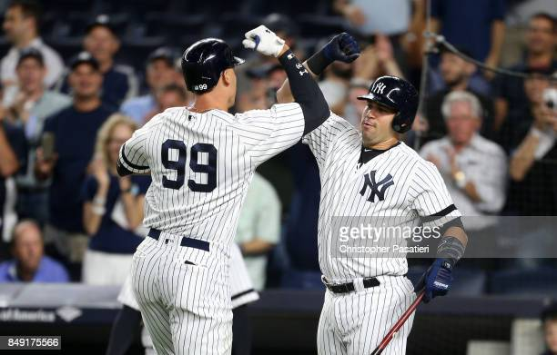 Aaron Judge of the New York Yankees is congratulated by teammate Gary Sanchez after hitting a solo homerun in the bottom of the first inning against...